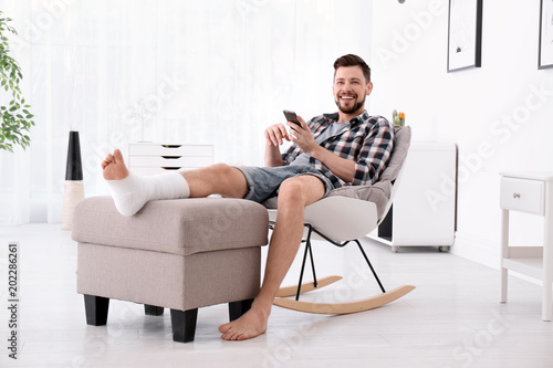 Fotografía  Man with broken leg in cast using mobile phone while sitting in armchair at home