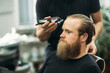 Bearded man having a haircut with a hair clippers