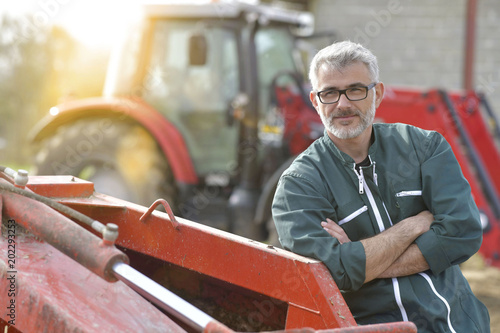 Farmer standing by tractor outside the barn