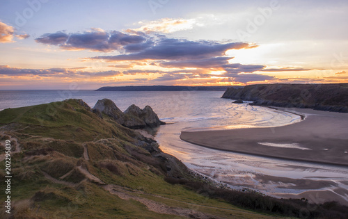 Photo landscape image of three cliffs bay at sunset with the tide in