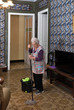 Older woman with mop making the floor of her house