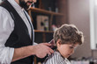 cropped shot of barber cutting hair of little kid with Hair Clipper