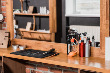 barber tools and spray bottles on counter at barbershop