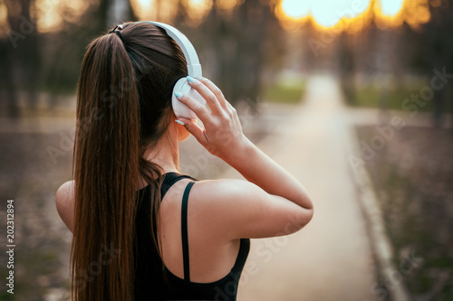 sports girl standing with back in bluetooth headphones at sunset in the park Wallpaper Mural