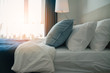 white and blue soft pillow on white bed sheet bedroom background with morning light