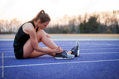 Athlete woman has ankle injury, sprained leg during running training Canvas Print