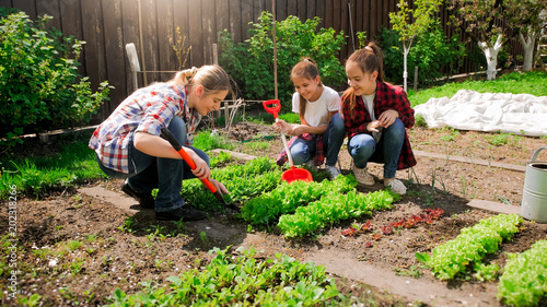 Tablou Canvas Happy young woman with daughters planting seeds in garden