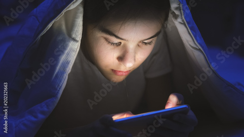 Closeup portrait of girl lying under blanket and playing on mobile phone