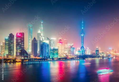 Aerial panoramic view over a big modern city by night. Shanghai, China. Nighttime skyline with illuminated skyscrapers.