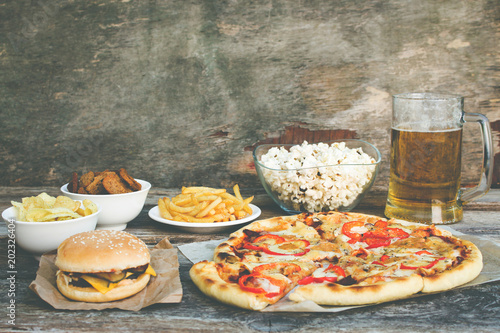 Fast food on old wooden background. Concept of junk eating. Toned image.  © Victoria М