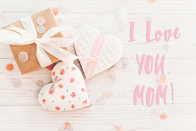 Mom I Love You Text On Pink Cookie Hearts On White Rustic Wooden Background With Confetti In Soft Light. Flat Lay. Happy Mother's Day Greeting Card, Top View. Cookie For Mom