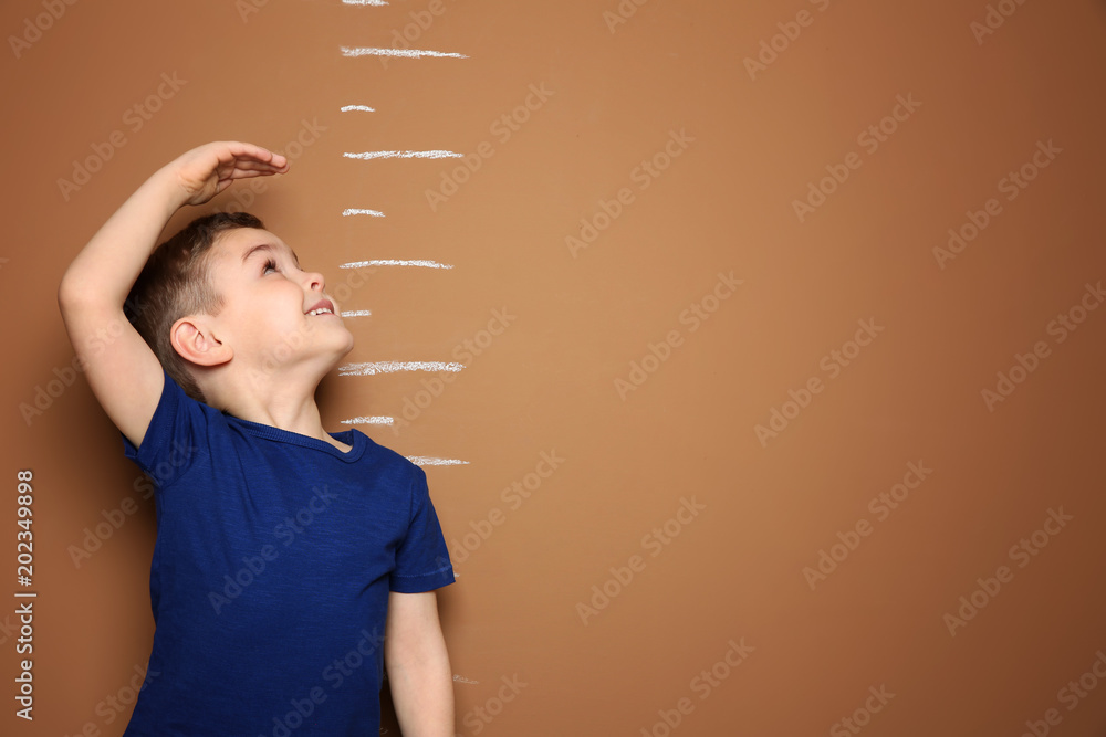 Fototapety, obrazy: Little boy measuring his height on color background