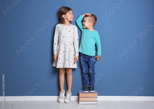 Leinwand Poster Little girl and boy measuring their height near color wall