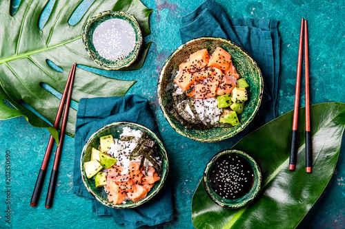 Foto  Hawaiian salmon poce with avocado, rice and sesamo served in bowls on tropical leaves