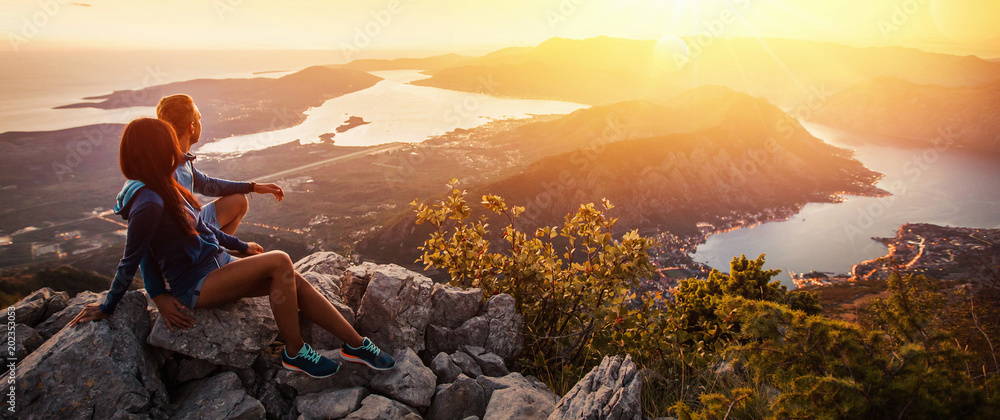Fototapety, obrazy: Happy couple watching the sunset in the mountains