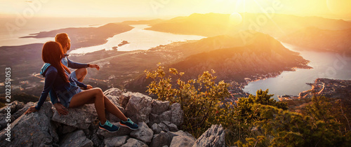 Fotografia  Happy couple watching the sunset in the mountains