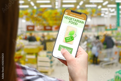 Vegetarian food idea, girl with frameless phone on blurred shop background