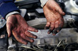 Hands of a mechanic in oil and fuel oil with a wrench during repair of the engine