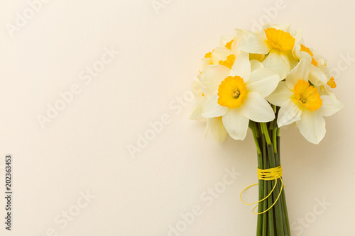 Papiers peints Narcisse White daffodil bouquet on yellow pastel background with copy space.