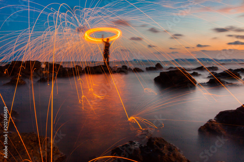 Photographie  A ring of fire spinning steel wool on the rock and beach, Showers of hot glowing sparks from spinning steel wool on the rock and beach