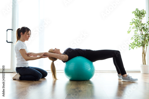 Fotografía  Physiotherapist helping patient to do exercise on fitness ball in physio room