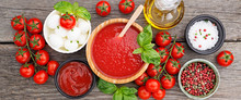 Ingredients For Cooking - Tomato Sauce, Pasta, Tomatoes, Garlic, Olive Oil On The Old Wooden Background. Top View.