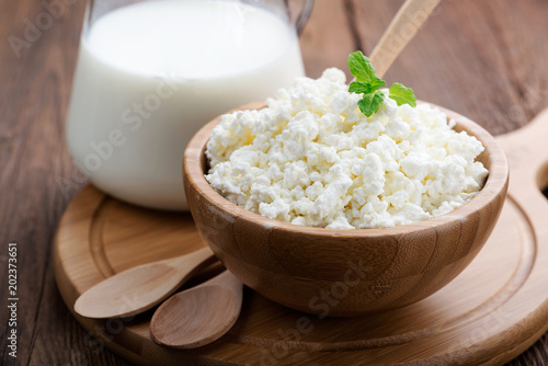 Homemade cottage cheese in a wooden bowl on dark wooden background Fototapete