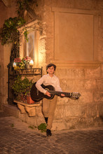 Street Urban Artist Musician Young Guy Playing Music On Retro Guitar In Old Narrow Vintage Streets Of An Ancient City