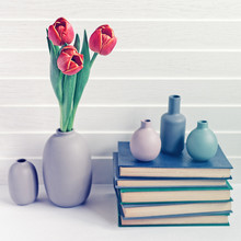 A Bouquet Of Three Red Tulips Is In A Gray Vase. Nearby Is A Pile Of Books And Bottles Of Bottles. White Wooden Background. The Image Is Suitable For A Greeting Card To A Writer Or Teacher.