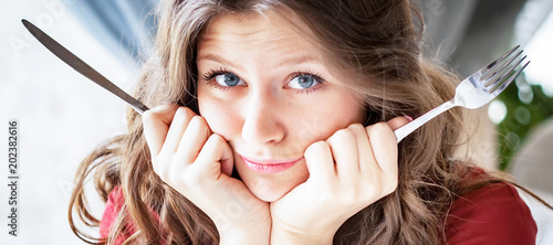 Portrait of hungry woman with fork and knife in hands Fototapet