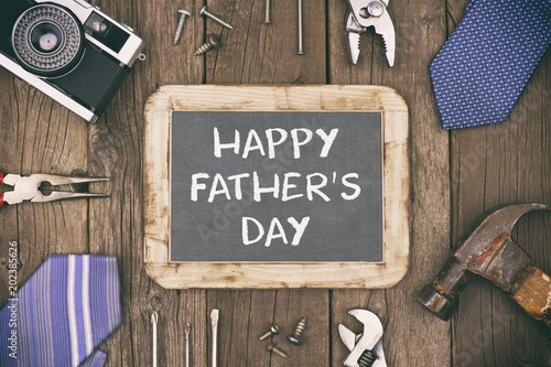 happy fathers day message on a chalkboard with frame of gifts ties and decor on