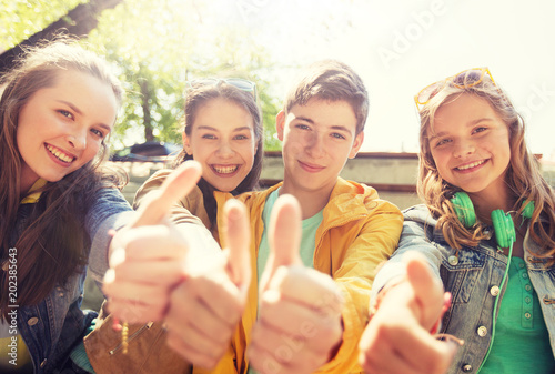friendship, gesture and people concept - happy teenage friends or high school students showing thumbs up