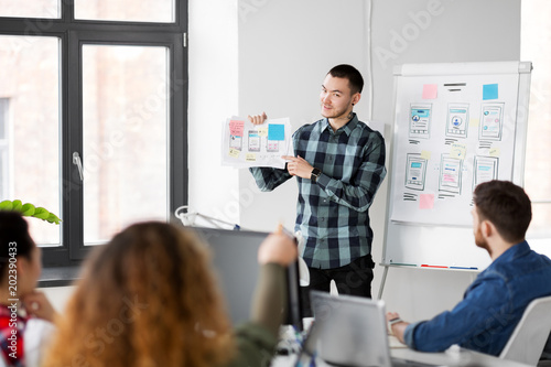 Fototapety, obrazy: business, technology and people concept - man showing user interface design on flip chart to creative team at office presentation