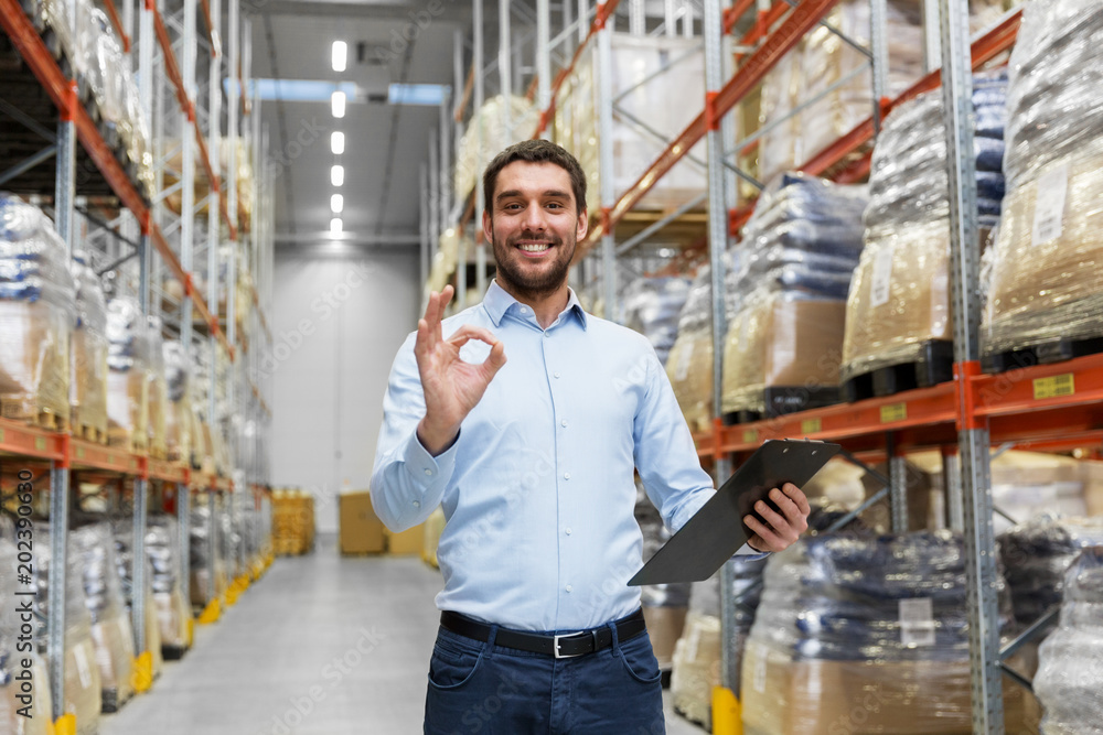 Fototapeta wholesale, logistic, business, export and people concept - happy man or manager with clipboard at warehouse showing ok hand sign