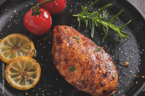 Tuinposter Buffet, Bar roasted chicken fillet breast with lemon tomato rosemary on a frying pan