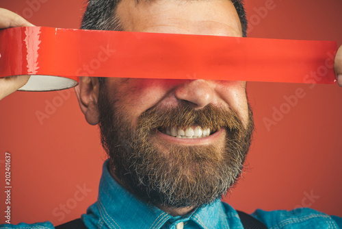 Fototapeta  Closeup happy man with duct tape over eyes