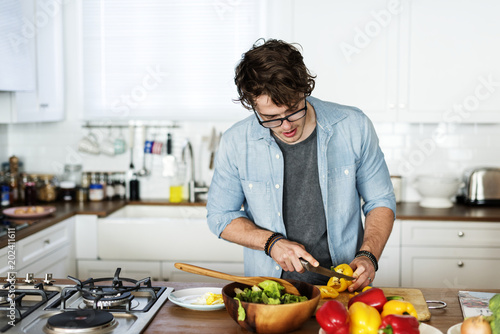 Poster Cooking Caucasian man cooking in the kitchen