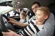 Young family choosing new car with salesman in salon