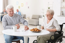 Senior Woman Playing Dominoes With Her Friend While Having Breakfast At Care Home