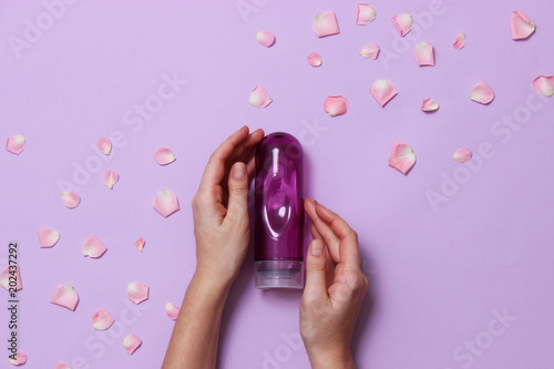 Fotomural an intimate grease on a pastel background in female hands and rose petals