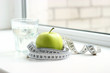centimeter tape, a green apple and a glass of water on a window sill against a light background. concept of a healthy diet, diet, sports.