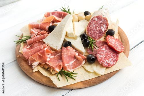 Tagliere con formaggio fresco, pane carasau, prosciutto crudo, salame e olive