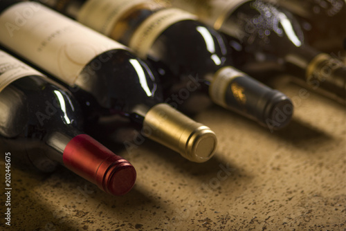 Cadres-photo bureau Bar Set of red dry wine bottles on cork background. Low depth of field.