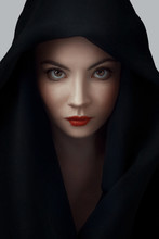 Woman Wearing Scarf With Hood. Beautiful Woman Big Eyes Covers Her Face With A Black Cloth. Red Lips Girl Under Hood. Isolated On Gray Background