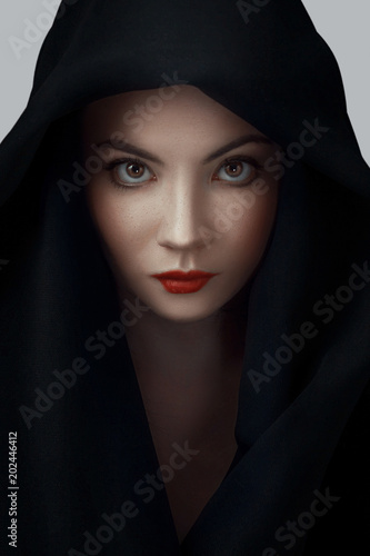 2ee2039588e Woman wearing scarf with hood. Beautiful woman big eyes covers her face  with a black
