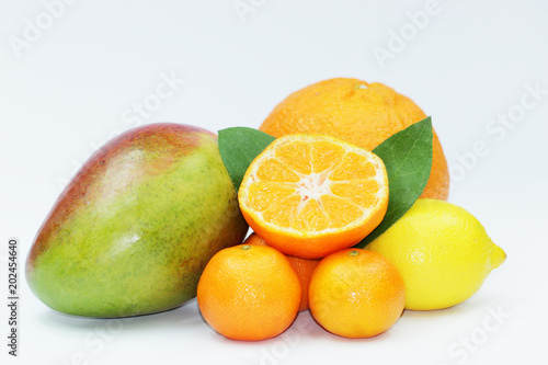 Fresh orange, mango, lemon and mandarins on white background