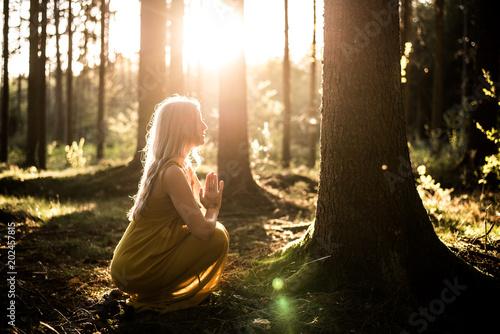 Fotografía  Junge Frau betet im Wald zum Sonnenuntergang