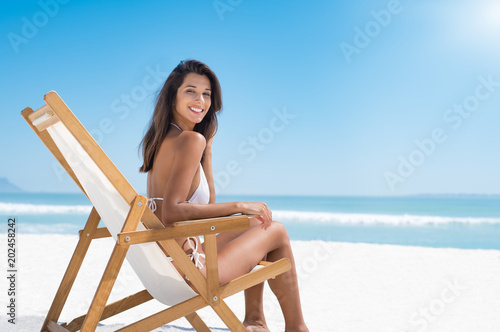 Fotomural Happy woman on deckchair at beach