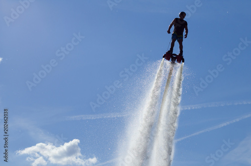 Flyboarding session in the aquamarine waters.. Fototapet