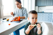 Mom and son prepare a salad in their kitchen